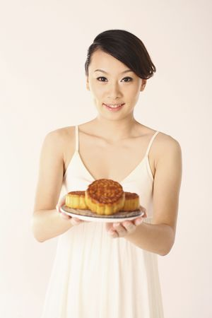 Woman holding a plate of mooncakes Stock Photo - 4630351