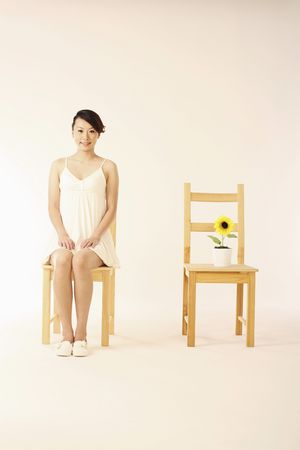 Woman sitting on chair, potted plant on the chair next to her