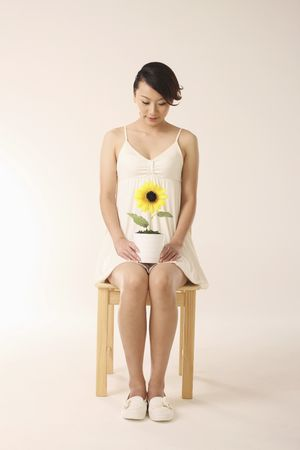 Woman sitting on the chair with potted plant on her laps photo