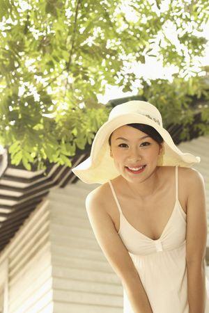 bending down: Mujer con sombrero agacharse sonriente