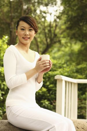 Woman holding a cup of tea, smiling photo