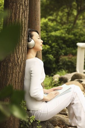 Woman leaning against tree, listening to music on the headphones