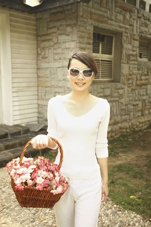 Woman carrying a basket of flowers Stock Photo - 4630286