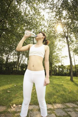 Woman in exercise clothing drinking water photo