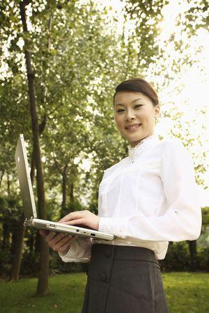 Woman holding laptop, smiling photo