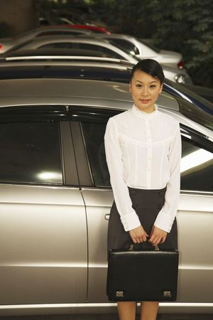 Woman with a briefcase standing beside a car Stock Photo - 4630172