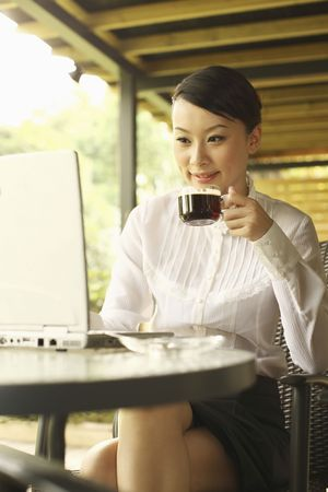 Woman enjoying a cup of coffee while using laptop in cafe photo
