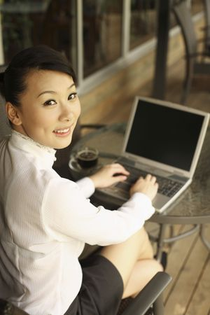 using the laptop: Woman using laptop in a cafe