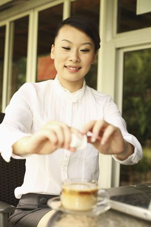 Woman pouring creamer into her coffee Stock Photo - 4630330