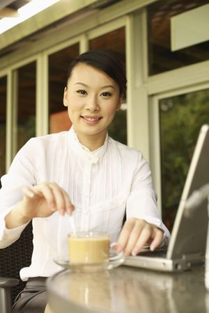 stirring: Woman stirring her cup of coffee, smiling Stock Photo