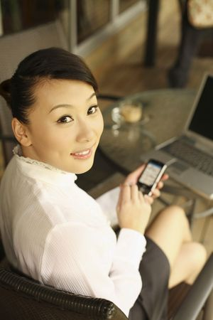 Woman holding PDA phone, smiling photo
