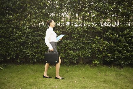 Woman with document and briefcase walking in the park photo