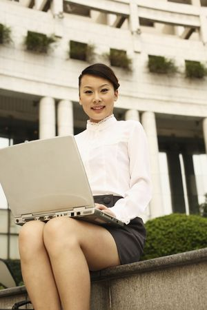 Woman with laptop on her laps, smiling photo