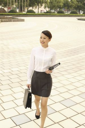 Woman with briefcase and organizer smiling while walking Stock Photo - 4630222