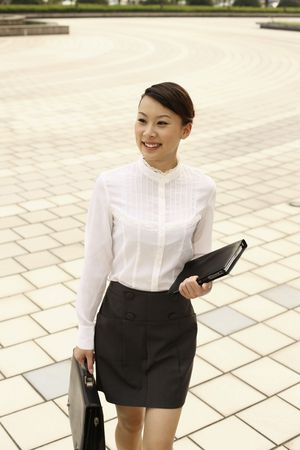 Woman with briefcase and organizer smiling while walking Stock Photo - 4630347