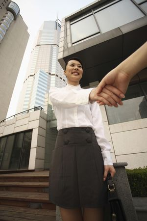 Woman smiling while shaking hands photo