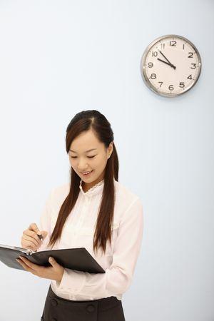 Woman writing on organizer Stock Photo - 4630365