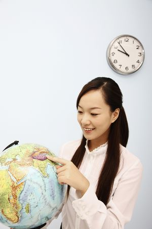 Woman pointing at globe photo