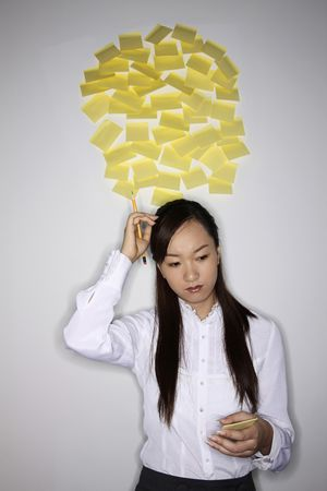 scratching head: Woman scratching head while thinking, some adhesive notes sticking on wall behind