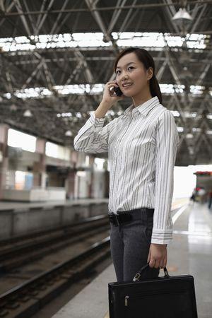 estacion de tren: Mujer de pie sobre la plataforma de la estaci�n de tren hablando por tel�fono