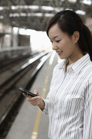 Woman standing on train station platform text messaging on the phone photo