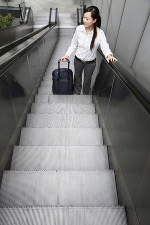 Woman going up escalator with suitcase photo