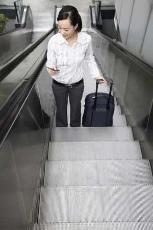 Woman going up escalator with suitcase, text messaging at the same time photo