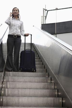 going down: Mujer bajando escaleras con la maleta, hablando por tel�fono Foto de archivo
