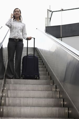 Woman going down escalator with suitcase, talking on the phone Stock Photo - 4630131