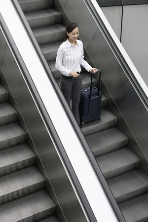 going down: Woman going down escalator with suitcase