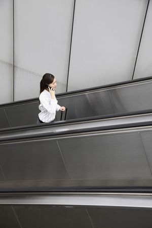 Woman going up escalator with suitcase, talking on the phone Stock Photo - 4630129