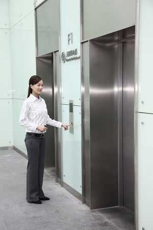 Woman pressing lift button photo