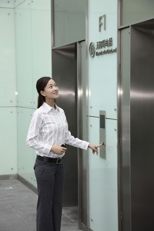 people in elevator: Woman pressing lift button