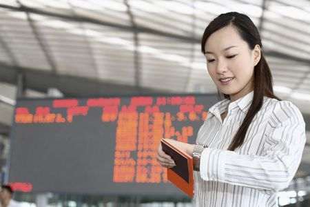 Woman with passport and plane ticket checking time on her watch Stock Photo