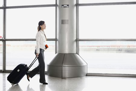 Woman walking through train station pulling suitcase photo