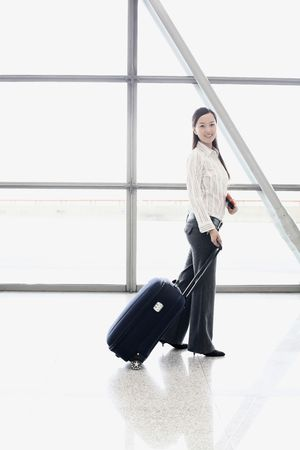 Woman with suitcase posing in train station photo