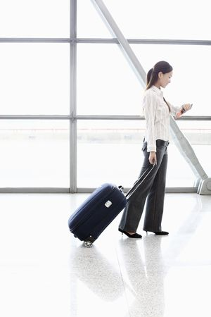 Woman with suitcase checking time on her watch photo