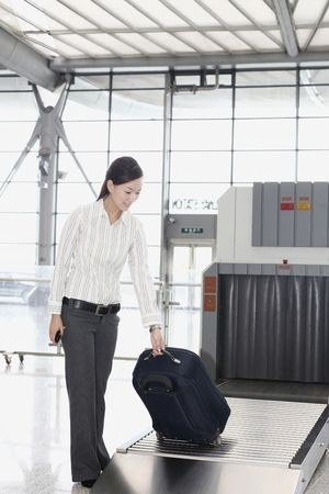 Woman picking her luggage from the airport carousel