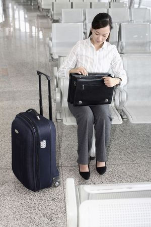 Woman checking her bag while waiting at train station Stock Photo - 4630305