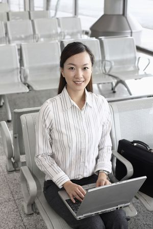 Woman using laptop while waiting at train station Stock Photo - 4630081