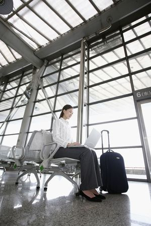 estacion de tren: Woman using laptop mientras espera en la estaci�n de tren Foto de archivo