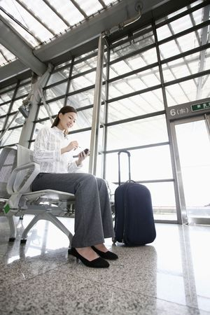 Woman using PDA phone while waiting at train station Stock Photo - 4630174