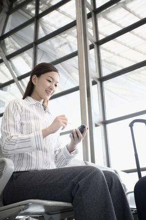 Woman using PDA phone while waiting at train station photo
