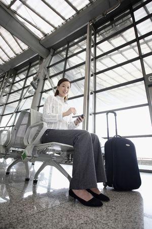 estacion de tren: Una mujer utilizando tel�fono m�vil y PDA a la espera en la estaci�n de tren Foto de archivo