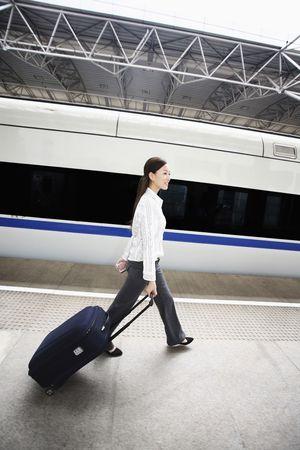 Woman walking on railroad station platform pulling suitcase Stock Photo - 4630155