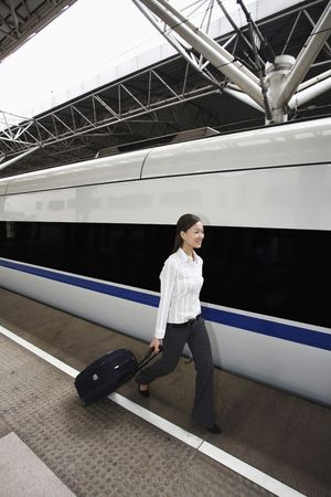 Woman walking on railroad station platform pulling suitcase Stock Photo - 4630209
