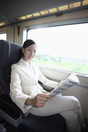 Woman reading newspaper while traveling on the train photo