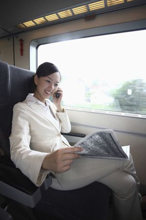 Woman talking on the phone and reading newspaper while traveling on the train photo