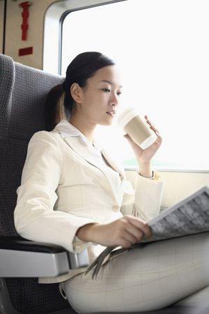 Woman reading newspaper and drinking coffee while traveling on the train photo