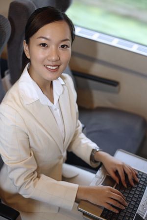 Woman using laptop while traveling on the train photo
